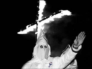 A white terrorist doing the Ku Klux Klan salute.